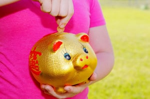 800px-Girl_Purring_Money_Into_Piggy_Bank