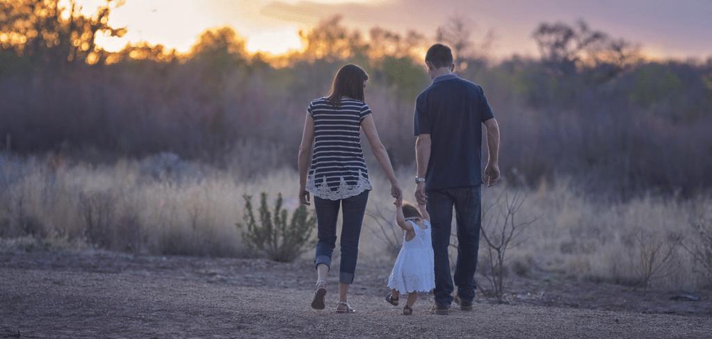 família andando em um campo com por do sol ao fundo, seguro de vida, segurança para os filhos, cuidado