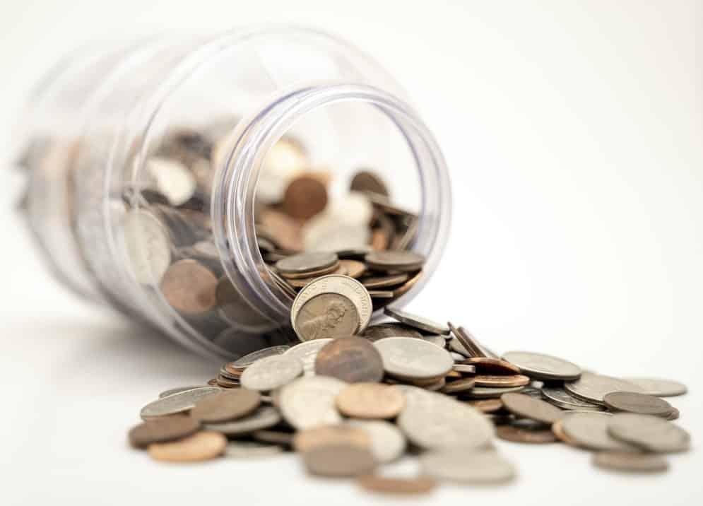 imagem de pote plástico tombado com moedas, em alusão a uma reserva de emergência