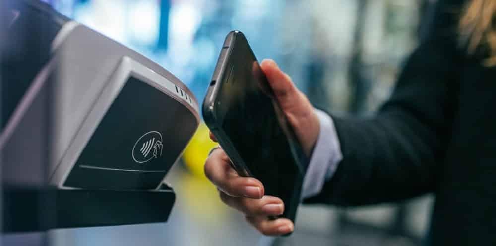 homem faz pagamento em fintech com celular, por meio de NFC e tecnologia